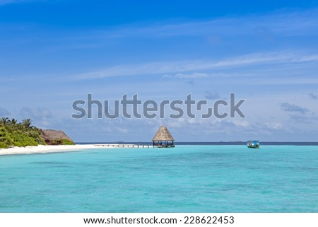 Jetty over blue ocean to island with boat anchoring in front - stock photo