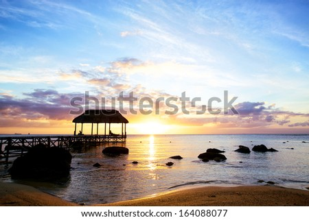 Jetty silhouette against sunset in Mauritius - stock photo