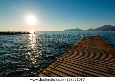 Jetty silhouette and island with beautiful sundown in ��l�¼deniz, Turkey - stock photo