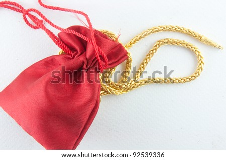 Jewel and gold bag on white background - stock photo
