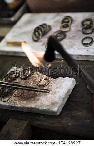 Jeweler crafting golden rings with flame torch. - stock photo