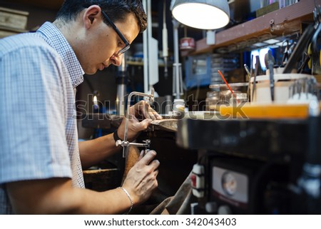Jeweler designing jewelry in workshop - stock photo