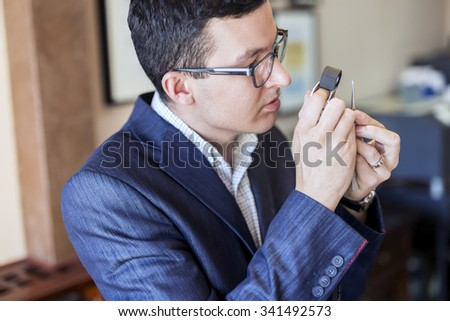 Jeweler looking at diamond through loupe to inspect it - stock photo
