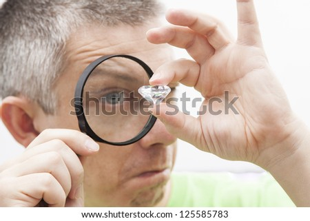 Jeweler looking intrigued at a diamond - stock photo
