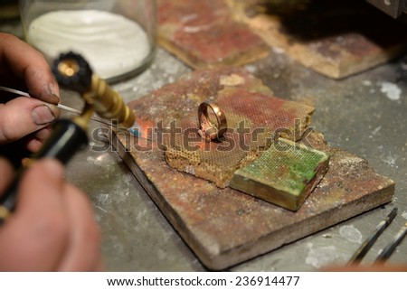 jeweler produces a ring of gold - stock photo