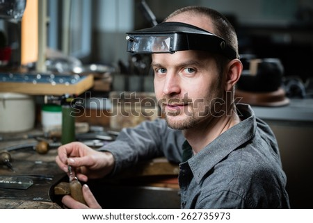Jeweler working on wedding gold ring in his workshop looking at the camera. - stock photo