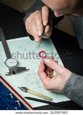 Jeweler working with wax model ring in his workshop. Craft jewelery making. - stock photo