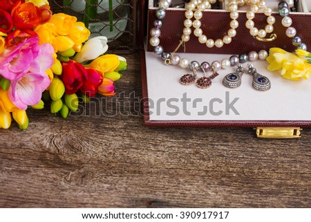 Jewellery in treasure box with fresh fresia flowers border on wood  - stock photo