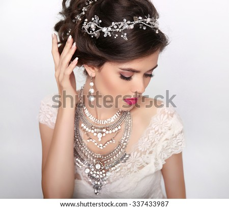 jewelry. Beautiful Fashion Luxury Hairstyle, Makeup. Beauty portrait. Wedding hair style. Young Woman isolated on studio background. - stock photo