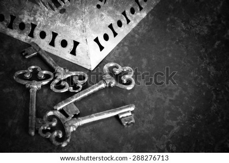 Jewelry box and four vintage keys. Retro aged toned photo with scratches. Black and white. Vignette. - stock photo