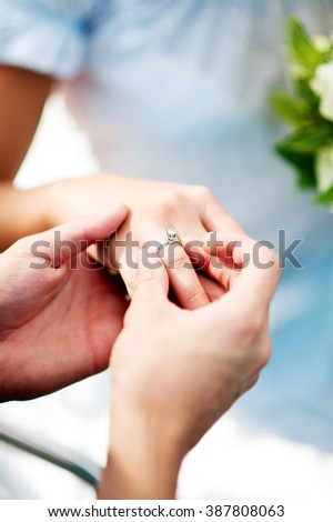 Jewelry, couple, love and wedding concept - close up of man and woman hands with engagement diamond ring in woman's finger. - stock photo