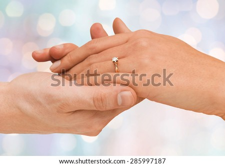 jewelry, couple, love and wedding concept - close up of man and woman hands with engagement ring over blue holidays lights background - stock photo