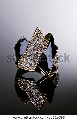 Jewelry photography. Gold ring with crystals on gradient reflective surface. - stock photo