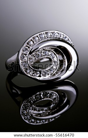 Jewelry photography. Silver ring with crystals on gradient reflective surface. - stock photo