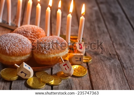 Jewish holiday hannukah symbols - menorah, doughnuts, chockolate coins and wooden dreidels. Copy space background. - stock photo