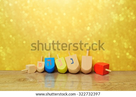 "Jewish holiday Hanukkah background with spinning top dreidel over gold bokeh. Copy space for text. The Hebrew letters are the first letters of the words ""A great miracle happened here."" - stock photo"