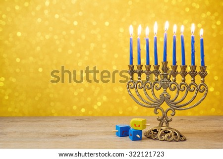 "Jewish holiday Hanukkah background with vintage menorah and spinning top dreidel over lights bokeh. The Hebrew letters are the first letters of the words which means ""A great miracle happened here."" - stock photo"