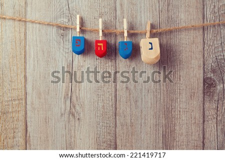 Jewish Holiday Hanukkah background with wooden dreidel spinning top hanging on string - stock photo