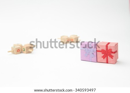 Jewish holiday hanukkah celebration - Dreidels, jug, oil, currencies, and gift boxes on a white background isolated - stock photo
