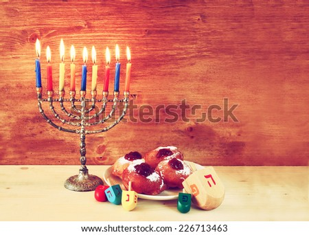 jewish holiday Hanukkah with menorah, doughnuts and wooden dreidels (spinning top). retro filtered image  - stock photo