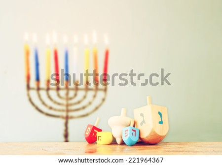 jewish holiday Hanukkah with menorah with wooden dreidels (spinning top).  retro filtered image - stock photo