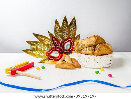 Jewish holiday of Purim. Hamantaschen cookies, gragger and carnival mask - stock photo