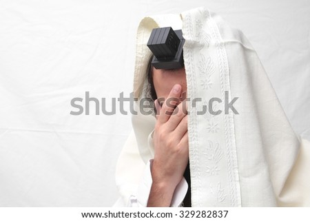 Jewish Man wrapped in tefillin And Talit And pray. A religious orthodox Jew with arm-tefillin on his left hand prays - stock photo