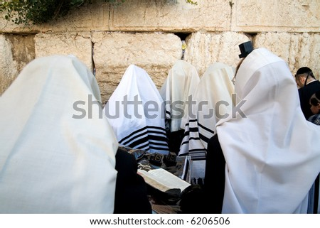 Jews in talitols being prayed in western wall. - stock photo