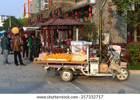 JIANGSU, CHINA - Nov 21, 2014:  People shop at fruit cart and food kiosks on street in Jiangsu, China. - stock photo