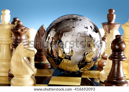 Jigsaw globe puzzle on chess board - stock photo