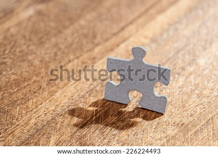 Jigsaw puzzle piece in a shape o f a man on a table. Shallow depth of field - stock photo