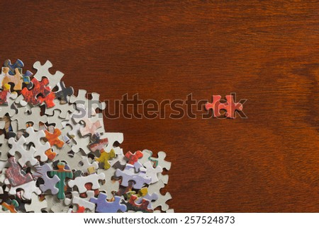 Jigsaw puzzle pieces in a pile with a single piece separated on a dark wooden table top. - stock photo