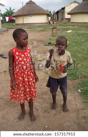 JINJA, UGANDA - June 18: An unidentified girl and boy aged 4 and 5 play with bubbles on June 18 2010 at an orphanage in a tribal village on the outskirts of Jinja, Uganda. - stock photo
