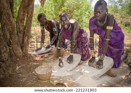 JINKA, ETHIOPIA - 10 August: unidentified beautiful girls from Mursi tribe in Mago National Park, Jinka, on 10 august 2014. Women are grinding cereals with a stone to prepare flour - stock photo