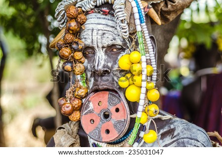 JINKA, ETHIOPIA - 10 AUGUST: unidentified woman from Mursi tribe with big lip plate, in  Jinka Ethiopia, on 10 August 2014. Between Mursi tribe, big lip plates are signs of beauty for a woman - stock photo