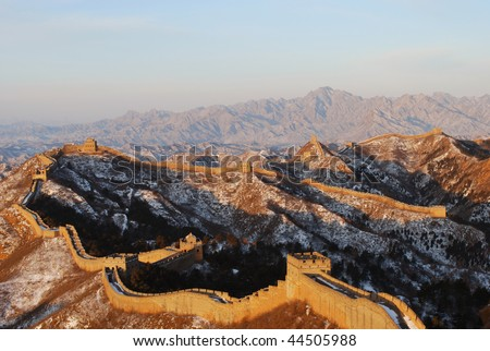 Jinshanling section of the Great Wall. Viewed from a distance, the Great Wall is like a giant dragon, curving its path over the mountain peaks whose line it follows. - stock photo