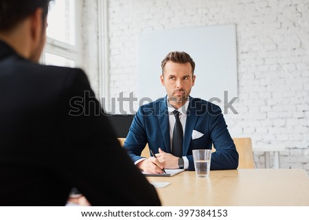 Job interview - businessman listen to candidate answers - stock photo