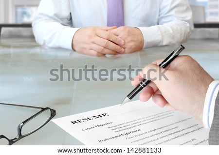 Job Interview in the Office with Focus on Resume and Pen - stock photo