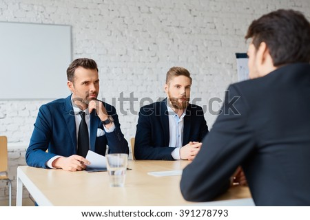 Job interview - two business man recruit candidate at their office - stock photo