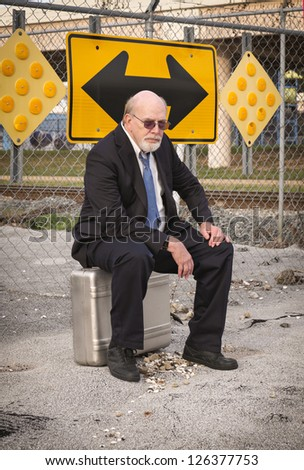 Jobless senior businessman sits on suitcase near railroad train tracks under a directional sign, pondering his uncertain future. - stock photo