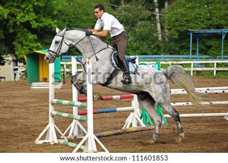 Jockey in glasses jump on horse over barrier on hippodrome - stock photo