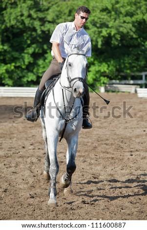 Jockey in glasses riding horse on hippodrome - stock photo