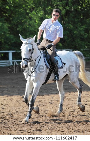 Jockey in glasses with whip riding horse on hippodrome - stock photo