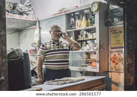 JODHPUR, INDIA - 16 FEBRUARY 2015: Local pharmacists talks on cell-phone before closing time. Post-processed with grain and texture. - stock photo