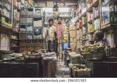 JODHPUR, INDIA - 10 FEBRUARY 2015: Three men in various merchandise store talk business. Post-processed with grain and texture. - stock photo