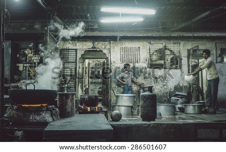 JODHPUR, INDIA - 07 FEBRUARY 2015: Two Indian workers in candy factory. Workers around India are underpaid, overworked and unhappy. Post-processed with added grain and texture. - stock photo