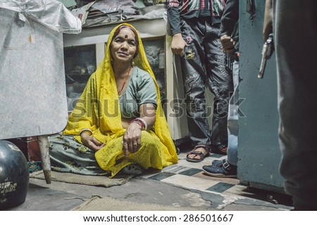 JODHPUR, INDIA - 16 FEBRUARY 2015: Woman sitting on floor of store while children stand next to her holding toy guns. Post-processed with grain and texture. - stock photo