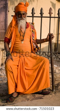 JODPUR, INDIA-CIRCA JANUARY 2008 : A bearded Holy Man in traditional orange robes sits outside the market in Jaipur, India, to give blessings to passers by circa January 2008 in Jodpur, India. - stock photo