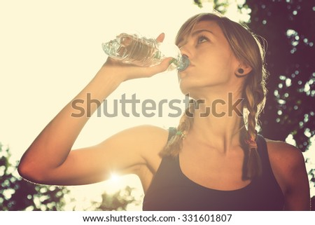 Jogger drinking water after hard exercise. - stock photo