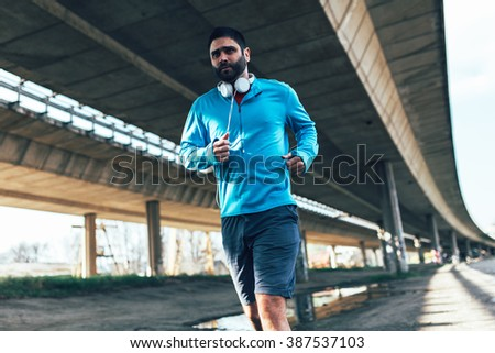 Jogger running in city environment. - stock photo
